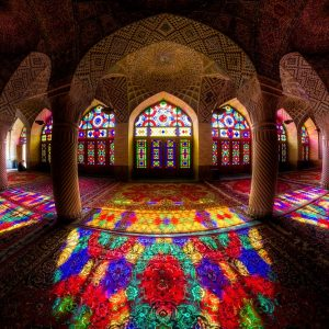The Pink Mosque, or Nasir al-mulk Mosque, is an historical site located in Shiraz, Iran. What makes it unique is the intricate mosaic work, the beautiful colored lights coming in through the stained glass windows and its dominant red color.  Only in the late Autumn and early Winter, when the sun is lower in the sky, does one have access to the intense, broad spectrum light inside the mosque. Also, this mosque is open to the public during scheduled times, and group of visitors frequently come and crowd the space.